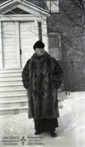 Depicts Fr. Boniface Heidmeier wearing a raccoon fur coat from Hudson's Bay store.